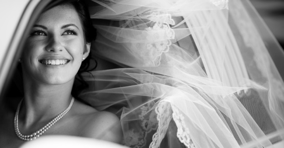Black and white image of a bride in a wedding car.